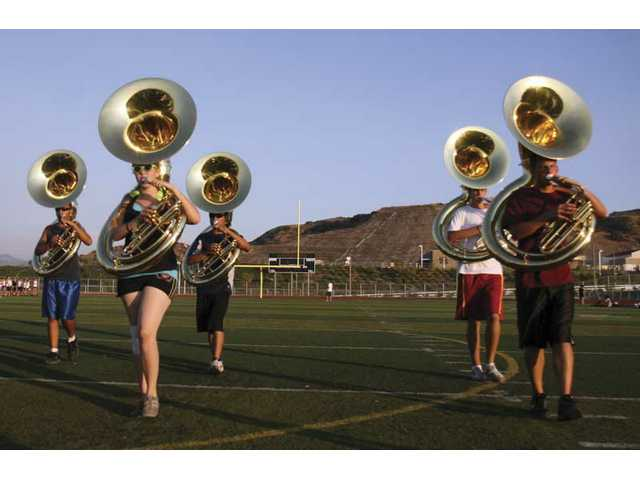 West Ranch sousaphone players march down the football field as they practice.