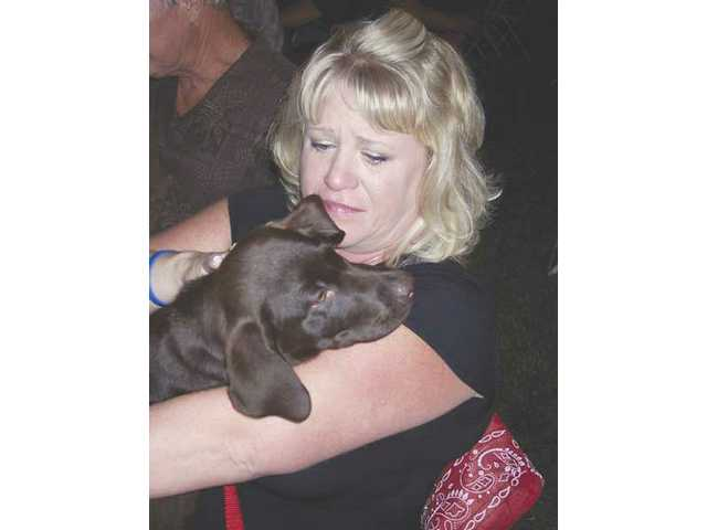 Katie Lakamp, of Saugus, cries as she holds her newly acquired chocolate lab puppy.