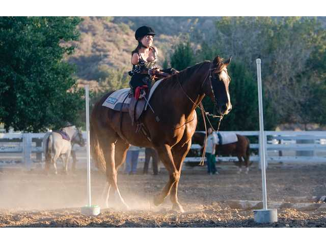 Dana Sachs demonstrates how she maneuvers her horse at the ranch.