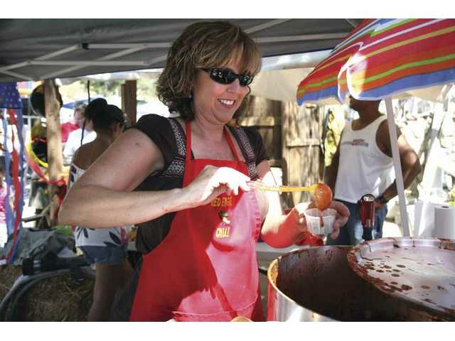 Susan Velazquez serves chili for the L.A. County Special Victims Bureau and L.A. County Fire booth at the 'Fun in the Sun Chili Cookoff' at the Jack Bones Equestrian Center in Castaic on Saturday afternoon.
