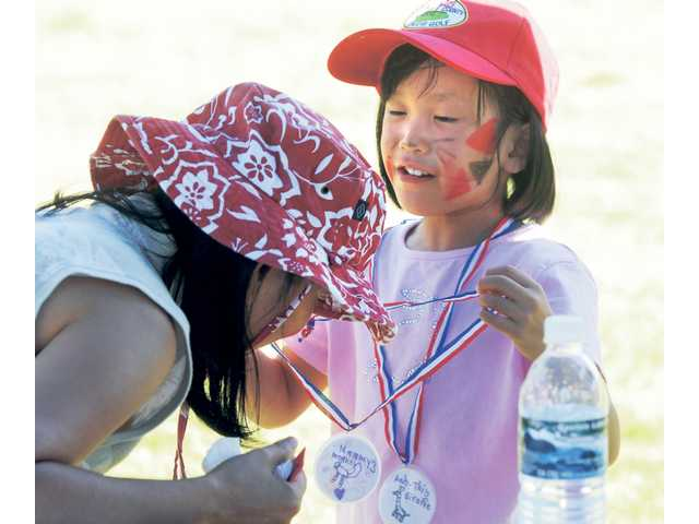 Ana-Thi Ta, 6, left, of Saugus, presents her mother, Ha Trinh, with a gold medal she made at the Celebrate Youth Sports Festival held August 29.