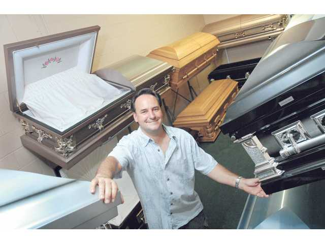 Roger Roberge displays a few of the wooden and steel caskets in the showroom of Wholesale Casket Warehouse in Santa Clarita