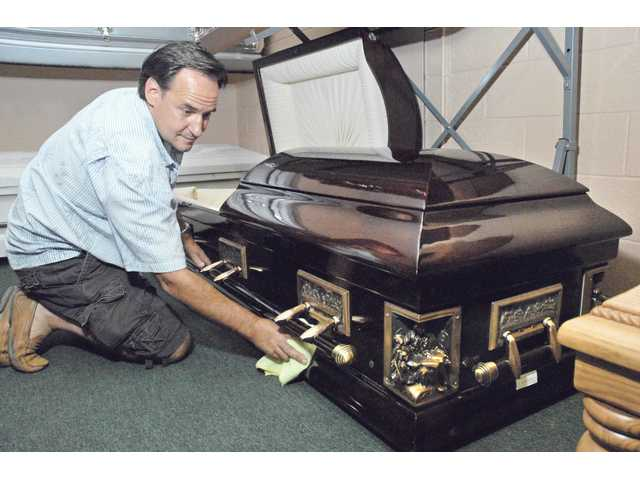 Roberge polishes a casket of poplar wood with Pietá corners and decorations depicting The Last Supper. Roberge recently opened  Wholesale Casket Warehouse on the advice of relatives, after business began to sag at Easy Riders, his entertainment-industry equipment rental company.