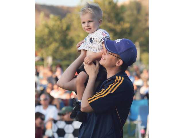 """Steve Snow dances with his son, Evan Snow, to the song """"Lively Up yourself,"""" performed by Urban Dread on Saturday at Concerts in the Park."""