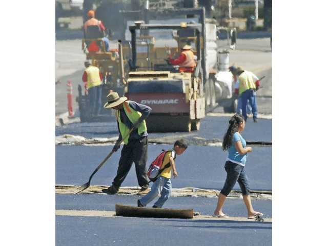 A woman and a young boy walk across Main Street near Market Street in Newhall as workers finish paving the street on Tuesday.