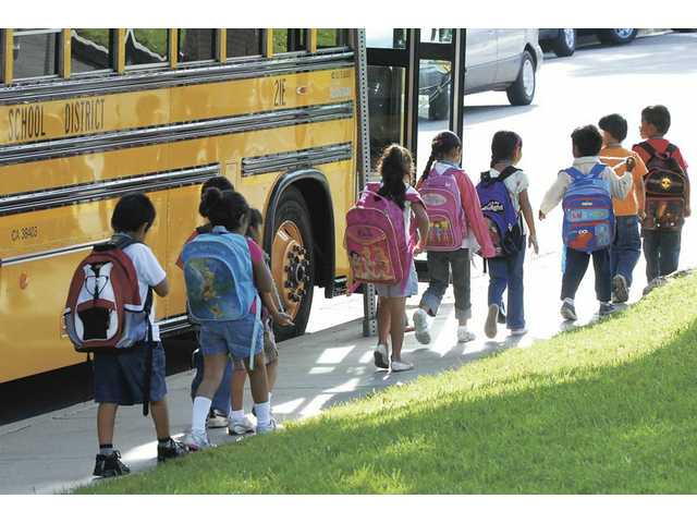 Elementary school children exit school buses and head to class in the Santa Clarita Valley. Three local school districts, Saugus Union, Sulphur Springs and Castaic Union, were forced to cut their school bus service due to the state budget crisis.