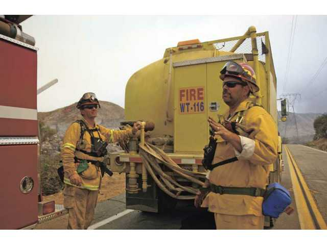 Warren Hubbard, right, from the El Dorado County Fire Department, talks with Jeff Burch of the Garden Valley Fire Department as they and their crews seek and destroy Station Fire hot spots along Aliso Canyon Road in Acton Monday afternoon.