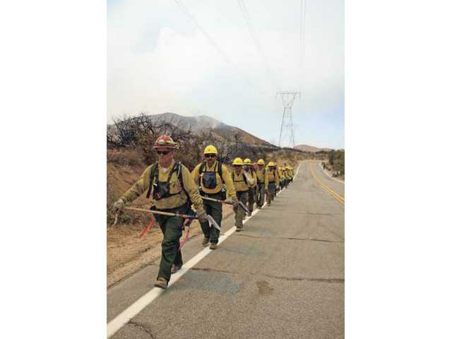 Members of the Scorpion 5 fire camp crew from Porterville, Calif., march down Aliso Canyon Road Monday afternoon after clearing some brush and killing hots spots from the Station Fire, which burned close to homes Sunday night.