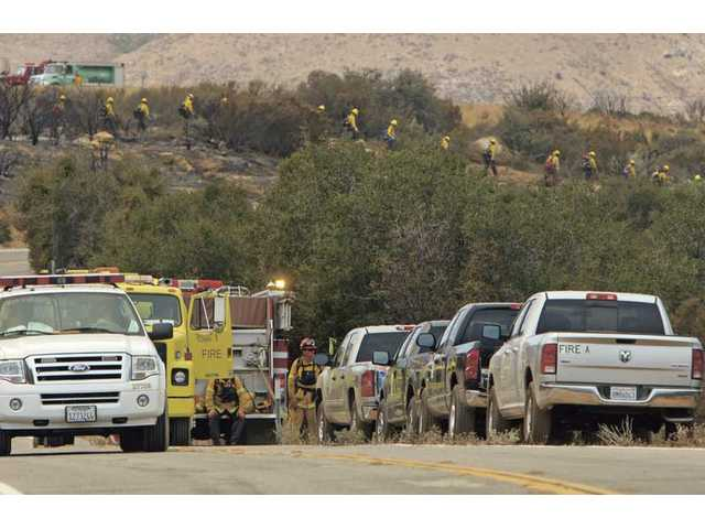 Camp crews and firemen mobilize on Aliso Canyon Road in Acton Monday afternoon. The Station Fire creeped near some homes along the road Sunday night, at times jumping the road.