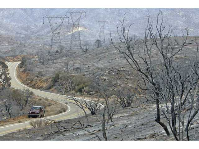 The Station Fire creeped through Acton Sunday night down Aliso Canyon Road. coming close to power lines and homes. Two homes were destroyed before thr fire moved east toward the Antelope Valley.
