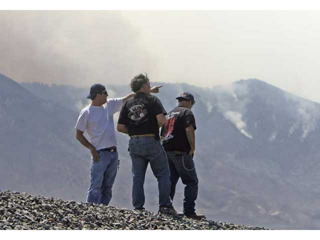 Acton residents and miners at the Acton Clay Quarries Thomas Lalonde, left, Dave Stewart, center, and Mike Heron look at the Station Fire creeping north over ridges from La Canada toward Acton Monday afternoon.