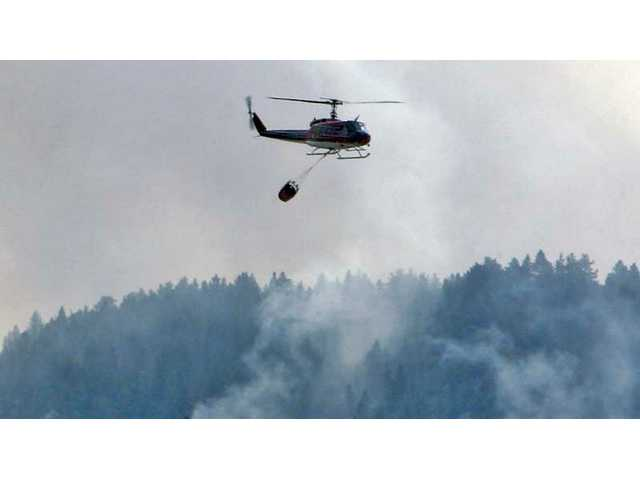 A water-dropping helicopter flies past smoky hillsides near Bootlegger Canyon Road in Acton Monday afternoon. The Station Fire destroyed two homes on its way through the Acton area Sunday night.