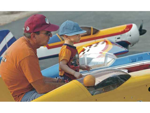 Bruce Picone and grandson Shane, 2, looks at some of the airplanes as they wait to fly at Canyon Crosswinds Flying Field on Saturday.