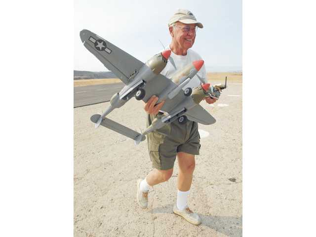Canyon Crosswinds Club President Gary Vollers carries an electric model of a WWII P-38 airplane at the Castaic flying field August 29. Members meet every Saturday morning to fly remote-controlled helicopters and airplanes.