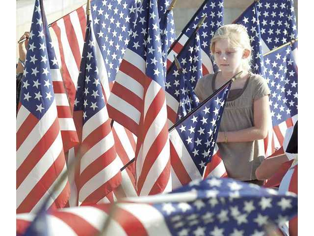 Jocelyn Wells, 7, was chosen to carry the flag to represent her second-grade class at dedication ceremonies.