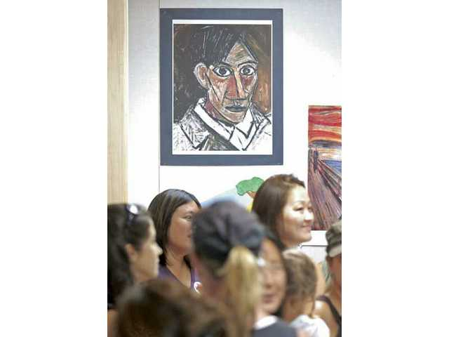 A self-portrait of Pablo Piccasso stares down from the wall in the new art studio at Stevenson Ranch Elementary School during a reception held at the dedication ceremony Thursday.