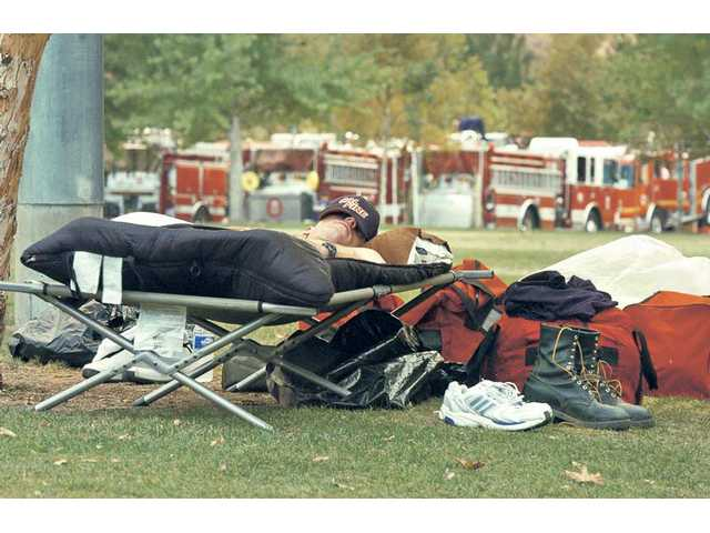 Firefighter Tom Gendron, of Santa Clara, sleeps Tuesday in the fire engine staging area at Central Park in Saugus as he and his crew wait for their 6 p.m. shift to start.
