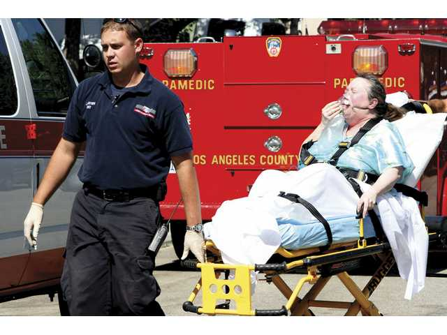A paramedic wheels the mother of Stevenson Ranch resident John Willett to an ambulance Tuesday, after Willett reportedly attacked his mother and grandfather after an argument escalated. Willett was arrested.