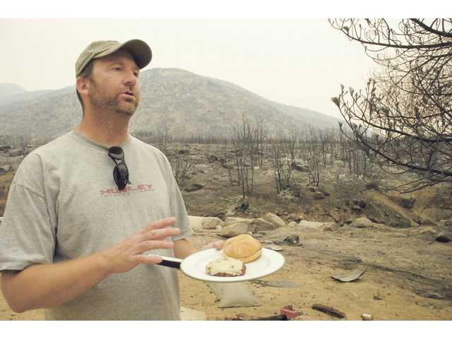 Aliso Canyon Road resident Scott Handley prepares to eat a hamburger he barbecued in his front yard amid the charred landscape of the Station Fire in Acton on Wednesday.