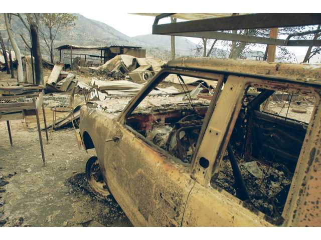 The burned out shell of a truck sits at the site of the caretakers house of the Montgomery Racnh vinyard on Aliso Canyon Road on Wednesday.