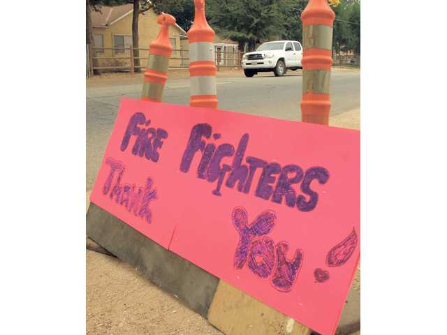 A sign sits on the side of Crown Valley Road in Acton thanking the firefighters for their efforts.