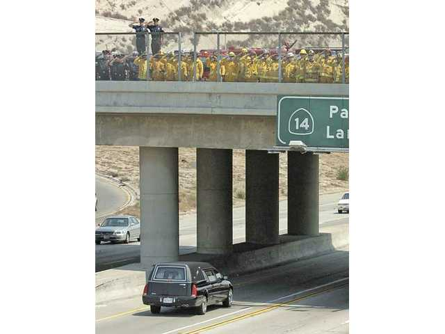 Hundreds of firefighters salute as they line the Sand Canyon bridge over the northbound lanes of Antelope Valley Freeway as a hearse bearing the body of Arnaldo Quinones, a firefighter who died in the Station Fire, passes under them on Thursday.