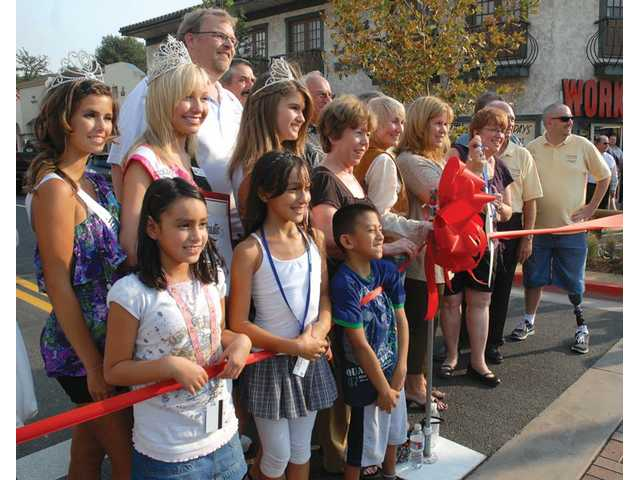 Karina Huerta, 8, left, and Melissa Espinoza, 9, of the Santa Clarita Community Center, hug the ribbon as they join dignitaries at the ribbon cutting of the first phase of Old Town Newhall Main Street streetscaping project on Thursday.