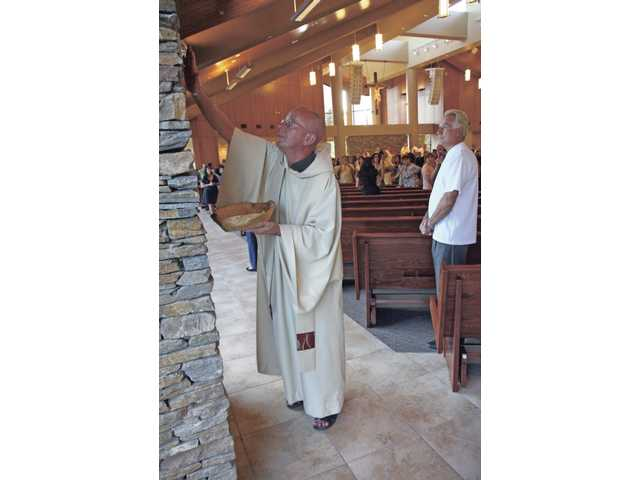 Reverend Blaise Brockman, an administrator at the Blessed Kateri Tekakwitha Catholic Parish, blesses the stone columns with oil during the dedication service Friday afternoon.