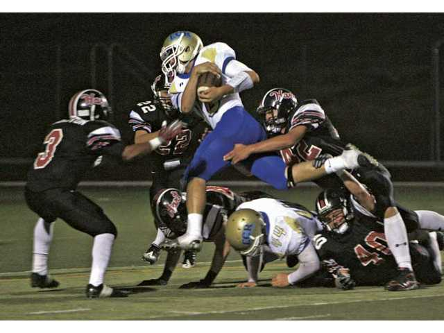 El Camino Real quarterback Ryan Meier, with the ball, leaps over Hart defenders at Cougar Stadium Friday. The Indians lost the game 33-28.