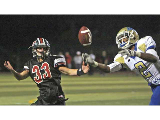 El Camino Real's Reggie Luckett (2) breaks up a pass intended for Hart's Ty MacArthur Friday at Cougar Stadium.