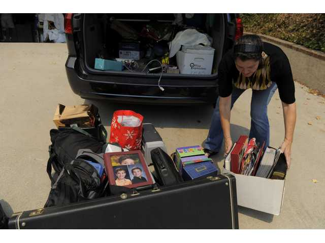Suzanne Goddard-Smythe unloads her belongings as she returns home after mandatory evacuation orders were lifted during the Station Fire in Glendale on Wednesday.