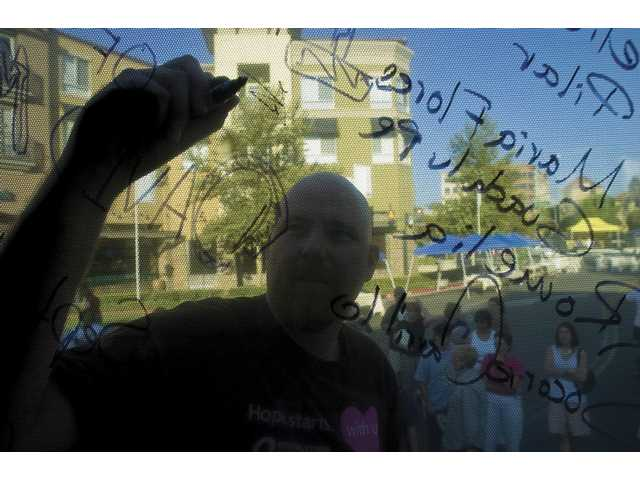 Tim Gibbs, of Sacramento, signs his name Friday on the window of an American Cancer Society bus that stopped in Valencia on a countrywide tour gathering signatures in support of cancer-related legislation.