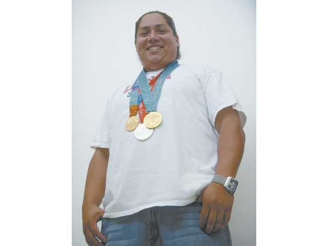 Crystl Bustos, a third baseman on the Team USA Softball Olympic team, a graduate of Canyon High, is shown recently in Newhall, wearing two gold medals and one silver medal.