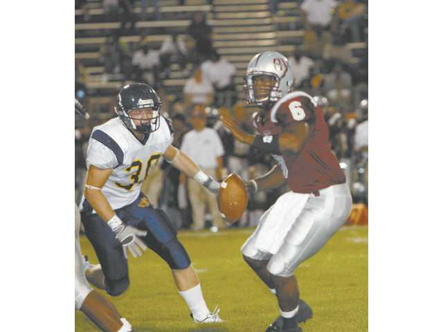 COC's Steve Gourley, left, draws a bead on Antelope Valley quarterback Rodney Dorsette late in the first quarter of the 2008 Foothill Conference opener in Antelope Valley. Gourely's hit caused a fumble which the Cougars recovered. Canyons won, 54-14.
