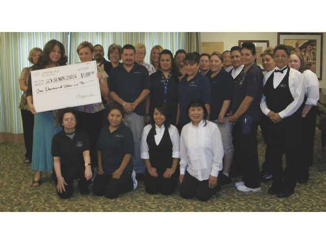 SCV Senior Center Health & Wellness Director Diana Sevanian accepts a check for $1,000 on behalf of the Senior Center from Summerhill Villa executive director Margie Veis and its employees. The money was donated to the Senior Center's Supportive Services Department in memory of Ruth Milne.