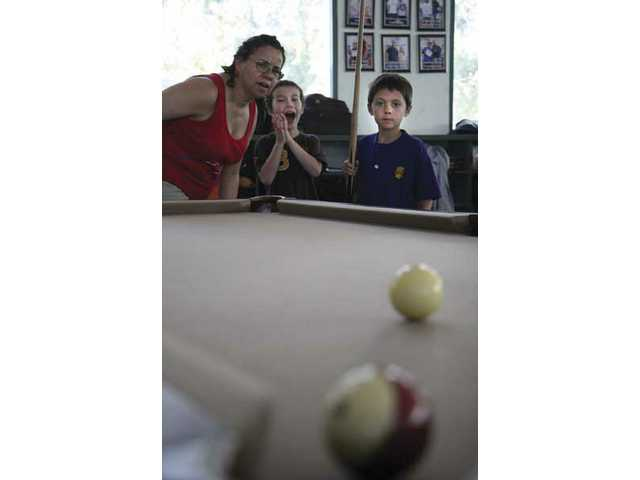 Linda Wood, left, James Kroman, center, and Jake Anderson keep a close eye on the cue ball to see if Anderson makes the shot.