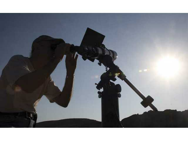 Steve Petzold, president of the Local Group Astronomy Club, gazes at the sun through a specially-outfitted telescope, Saturday at Vasquez Rocks Natural Area in Agua Dulce.