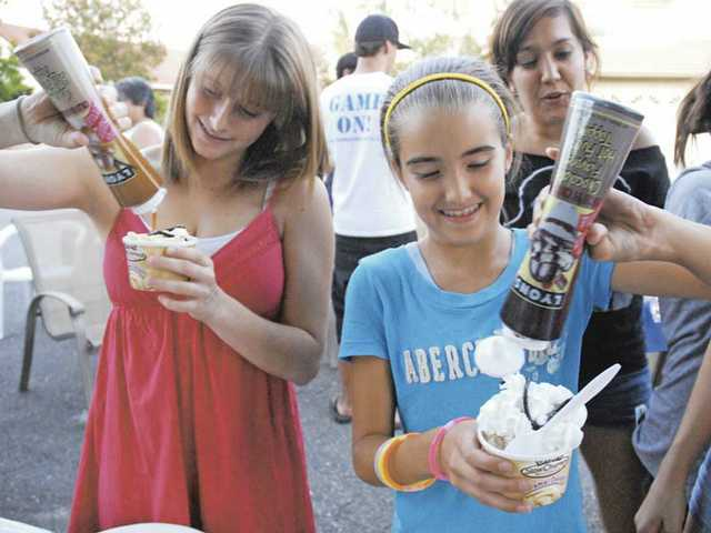 Jill Quinn, 18, and Brenna Radding, 11, pile on toppings to their Dreyer's ice cream at a block party on Red Cedar Place in Saugus on Saturday. Dreyer's Slow Churned Neighborhood Salute awarded residents of Red Cedar Place with ice cream for helping raise funds for Tom Bolewski, a recovering quadriplegic.