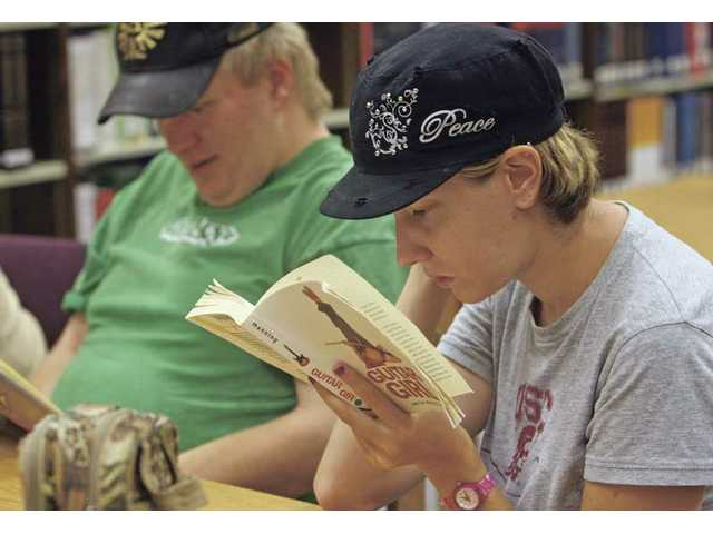 "Brittany Buckingham, 25, reads ""Guitar Girl"" at the Valencia Library Thursday afternoon through the program All People Access Community Services. APAC provides training, education, and general assistance to adults with development disabilities."