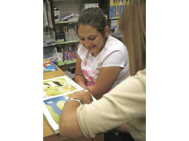 All People Access Community Services program instructor Shawna Kim, right, helps Karla Aguilar, 27, improve her reading skills at the Valencia Library on Thursday.