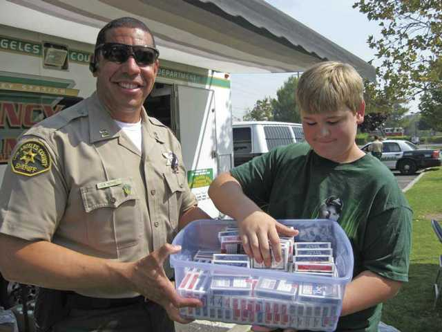 Santa Clarita Valley Sheriff's Station Capt. Anthony La Berge accepts cards for firefighters camped in Central Park from La Mesa Junior High student Adam Engberg.