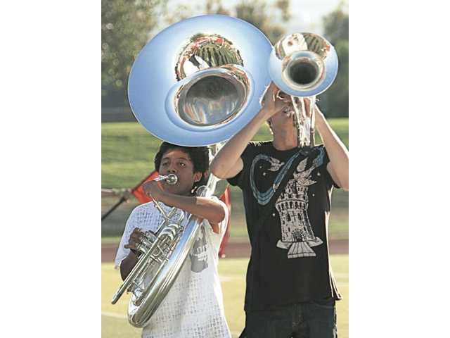 Oscar Sanchez, left, and Cameron West of the Hart High Regiment Band rehearse for their first football game halftime performance on Friday.