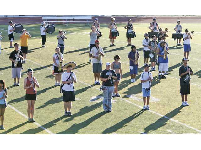 The Hart High Regiment Band rehearse the musical number Winter for their first football game halftime performance on Friday at a 12 hour band practice in 103 degree heat on the Hart High football field on Saturday.