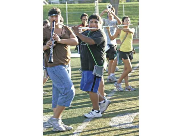 From left, Kaitlen Hansen, Luigi Jarez, and Lauren Estrada of the Hart High School Regiment Band march during practice on the Hart High football field on Saturday.