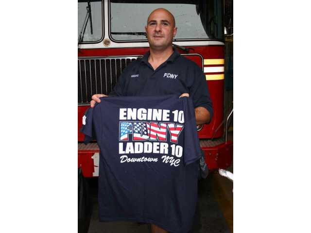 A member of the Firehouse 10 crew displays one of the t-shirts sold there to a steady stream of visitors to Ground Zero. Proceeds go to charity.