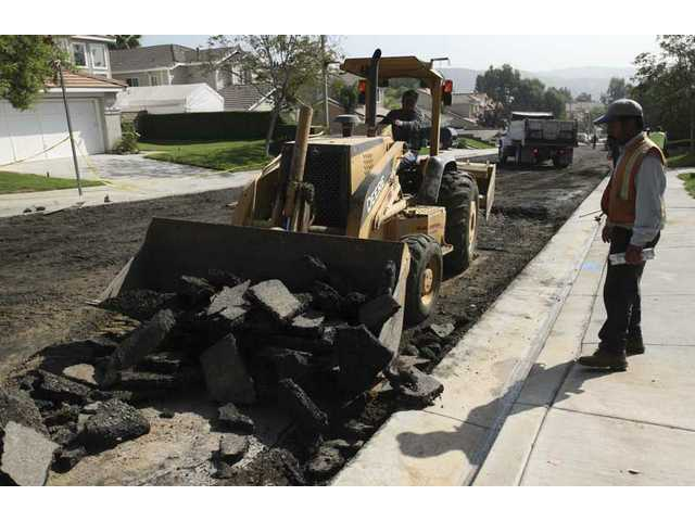 Employees with R.C. Becker and Son Construction Co. help clean up damaged asphalt on Lassen Street in Castaic Wednesday after an underground water main burst, opening up a sinkhole and flooding the residential street.
