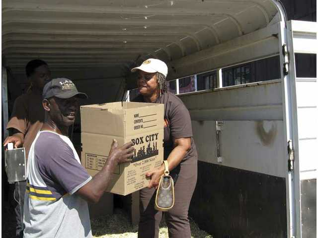 Volunteer Joe Bonner (left) helps Mayisha Akbar, founder and program director for the Compton Junior Posse, load boxes into a horse trailer on Tuesday.