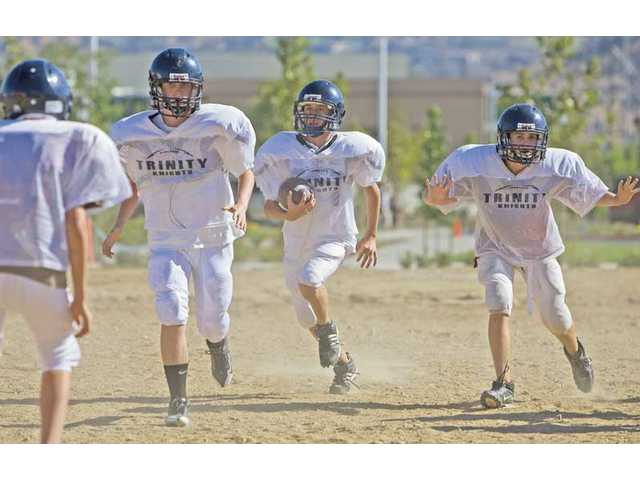 Trinity Classical Academy 9th-grader Kevin Tait, center, runs the ball as teammates attempt to block during practice Wednesday in Saugus. On Saturday, the Knights will play the first football game in program history when they field a junior varsity 8-Man team against Calvary Baptist at First Lutheran High in Sylmar.