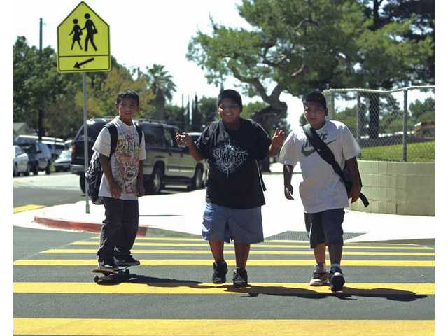 (Left to right) Canyon Springs Community School students Angel Hernandez, Luis Vargas and Marvin Gonzalez use a newly painted crosswalk as they walk home from school on Aug. 26.