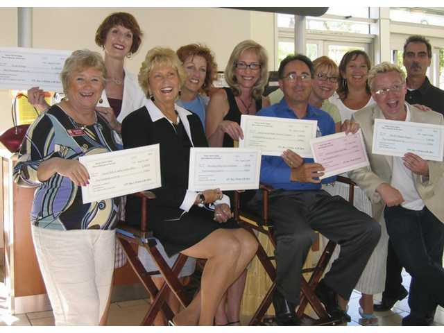 Flashing checks received from the 2008 SCV Man and Woman of the Year are, (right to left) Christine Miller (Zonta Club), Colleen Shaffer (Circle of Hope), Judy Penman (2008 Woman of the Year), Brigette Loden (Providence Holy Cross Foundation), Diane Green (SCV Disaster Coalition), Carl Goldman (2008 Man of the Year), Karen Maleck-Whiteley (Zonta Foundation), Andrea Slominski and Mark Salyer (SCV Theatre Project) and Stephen Peeples (SCV Disaster Coalition). The donations, totaling $4,000, were the net proceeds of 2008 SCV Man & Woman of the Year event presented to the sponsoring nonprofits of the honorees.